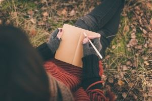 Woman sitting on the ground writing in her notebook