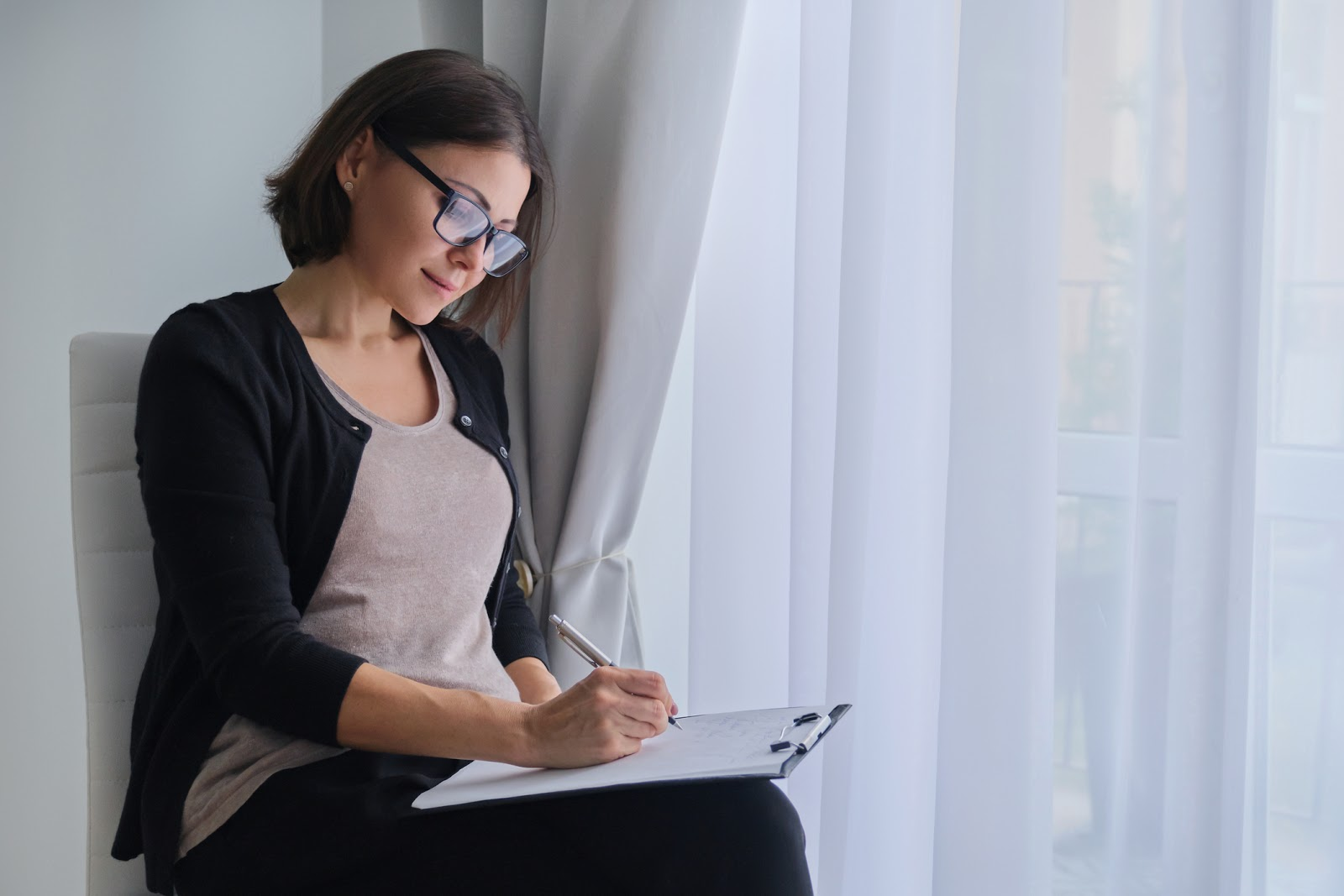 A woman with glasses sitting down filling out paperwork on a clipboard